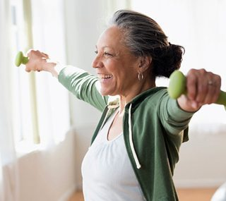 A smiling woman exercising with hand weights