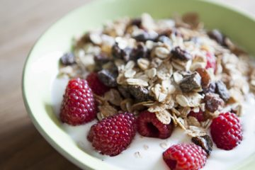A bowl of yogurt topped with raspberries and dried fruit