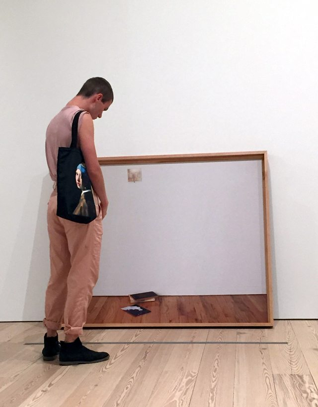 Photo of man looking at artwork in a museum