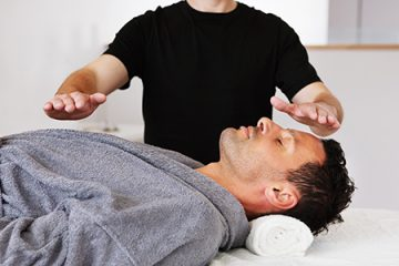 A man performing Reiki on a male patient on a cot