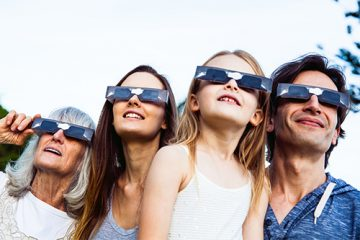A family wearing dark glasses while looking to the sky