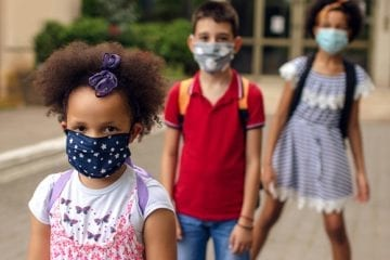 Children wearing masks outside a school that is reopening.