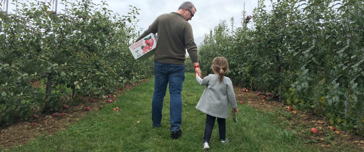 A photo of Peter McKay and his daughter walking through an apple grove