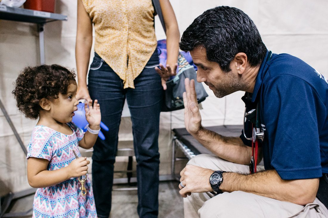 Dr. Chris Tedeschi with a young patient in a federal medical shelter in Puerto Rico