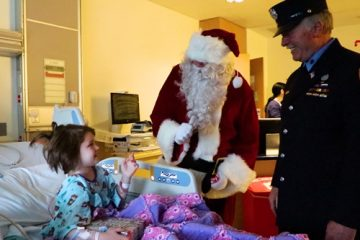 Santa Claus and a firefighter visiting a pediatric patient