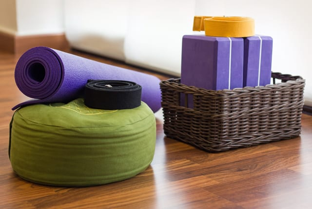 A rolled-up yoga mat and blocks