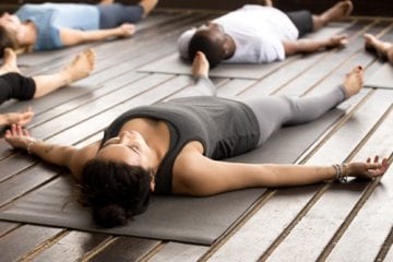 A woman lying on a mat in a yoga class