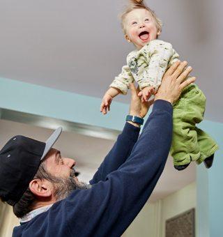 Cesar Baptista lifting a smiling Dashiel into the air