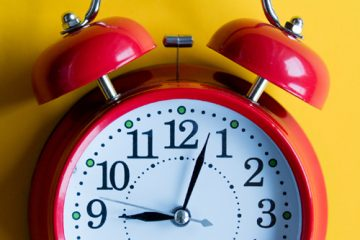 A red clock against a yellow background
