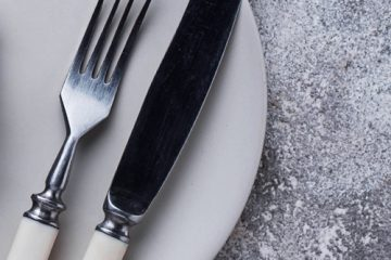 A knife, fork and clock on a plate