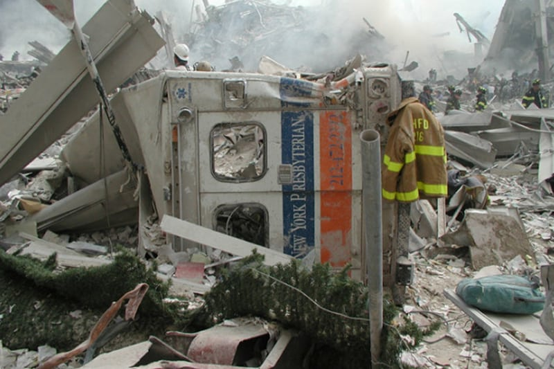 A destroyed emergency vehicle in a pile of rubble