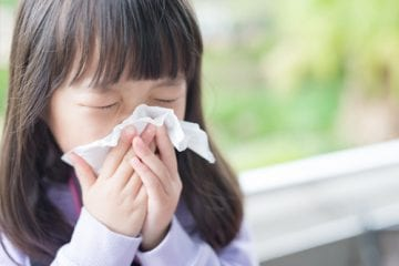 A girl sneezing into a tissue