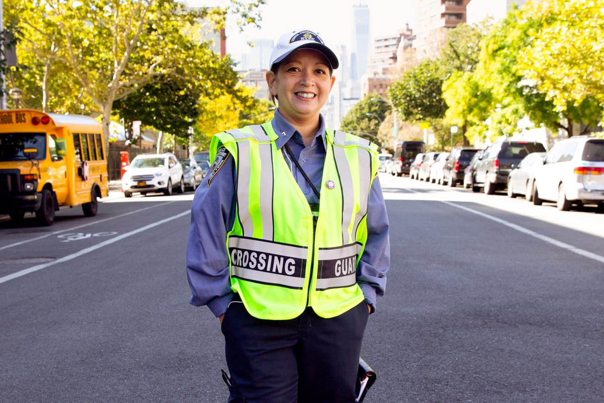 A female crossing guard smiling
