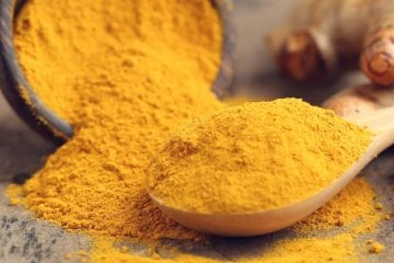 Powdered tumeric in a measuring spoon