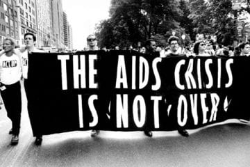 "Marchers with a banner that says ""The AIDS Crisis Is Not Over"""