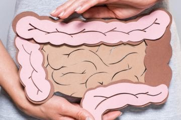 Woman holding collage of large and small intestine to connote bloating