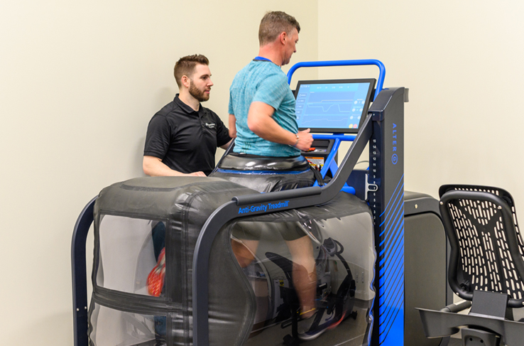 A man running on a treadmill while being watched by a healthcare provider
