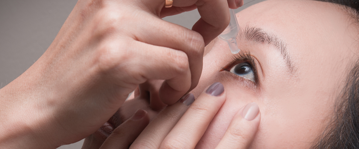 Photo of woman adding eye drops to eye