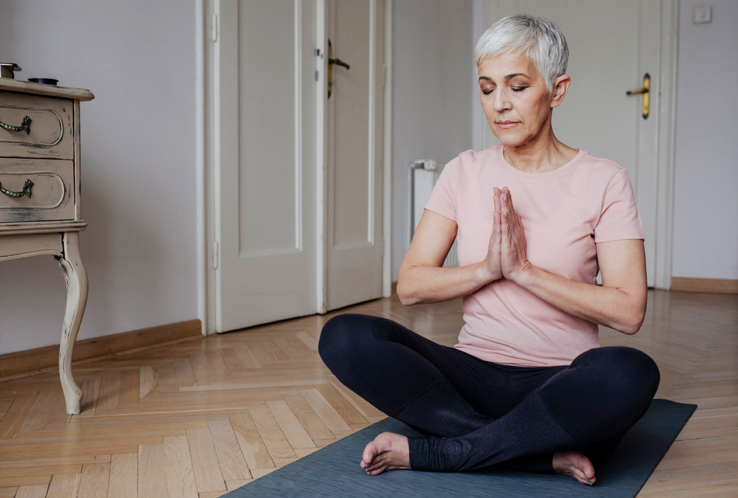 An older woman meditating, one way to help boost your immune system.