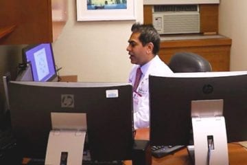 Dr. Rahul Sharma in front of a computer screen for a virtual healthcare visit