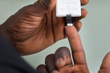 A person with diabetes uses a device to check blood sugar