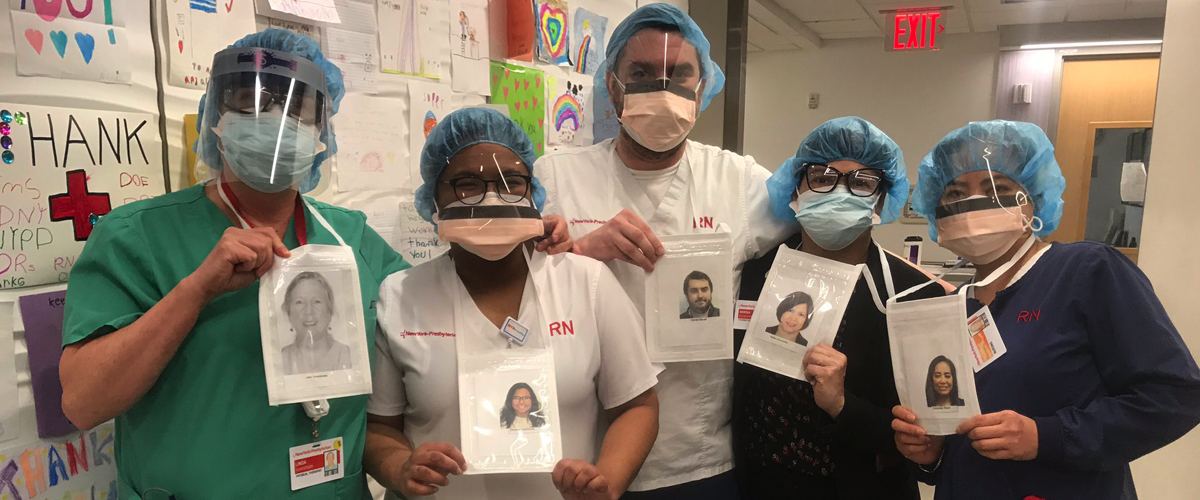 Clinical staff wearing masks hold photos of themselves