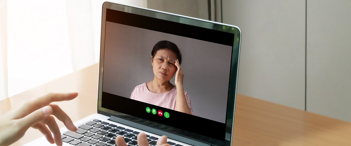 Woman on a laptop computer screen has a headache
