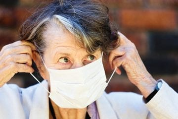 Senior woman removing a face mask.