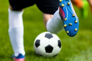 Cleated shoe kicking a soccer ball