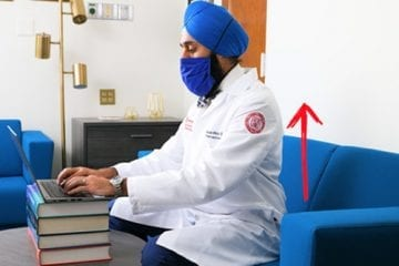 Dr. Singh sits at a laptop, a red arrow pointing up superimposed near his back to show good posture