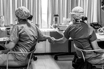 Two healthcare workers holding hands while receiving the COVID-19 vaccine