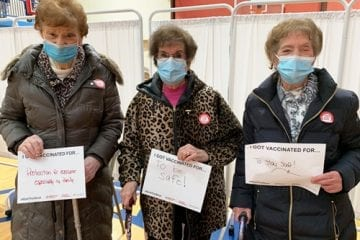 Three senior women holding signs saying why they got their vaccine
