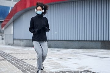 Woman running outdoors, wearing a mask.